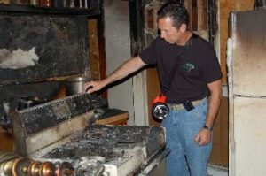Mickey Grasso examines a kitchen range